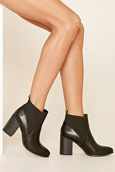 A pair of faux leather chelsea boots with a block heel, a pull tab, and a slightly pointed toe.