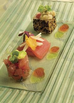 Raw tuna trio: seared tuna with white bean salad, Carpaccio of tuna with fennel and oranges, and tuna tartare with avocado. The Catered Affair, Boston, MA; Photography: Ron Manville