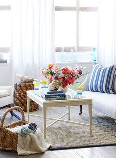 Wicker baskets, a jute rug and white coffee table get a jolt of fresh, nautical style from the addition of bright pink florals and navy and white stripes.