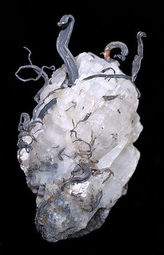 Wires of native silver emerging from a calcite crystal. Source: Kongsberg Silver Mining District, Svene, Flesberg, Buskerud, Norway.