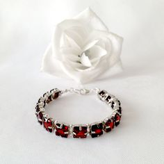 The Red Princess 8 inch tennis bracelet and 1.75 inch earring set each features a series of 3 carat square cut dark red Cubic Zirconia with sterling silver embellishments and findings.