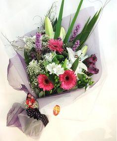 RAMO VARIADO JOSEFINA Delicado ramo variado, con gerberas, liliums, astromelias y otras flores de estación, en tonos lila, rosa y blanco, envuelto con tul y cinta de tela, con detalle de flores en el moño.