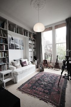 Library to guest room: Disassembled foldaway sofa down to box containing mattress, added upholstered fold up lid, cladded and trimmed out box, and surrounded by builtins. Seat folds up to be headboard and bed folds out. From ao at home