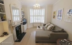 victorian terrace sitting room, corner sofa, plantation shutters, edwardian fireplace SHOOTFACTORY: london houses / Fawe, London SW15