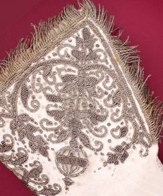 A Coronation Glove, Elizabeth I. White alum tawed sueded leather, left hand gauntlet glove. Prix seams, all hand sewn. The cuff is decorated with silver thread, purl and sequins, and silk satin inserts in a stylized design showing an Orb, flowers and leaves. Lined. The cuff is lined with dark cream/beige silk fabric. Turned top, with the silk lining hiding the seams inside. The edge of the cuff is trimmed with twisted thread fringing.