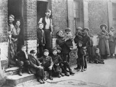 Men and young boys stand outside one of the many lodging Houses, or Doss Houses as they were known, in London's East End, 1880s.