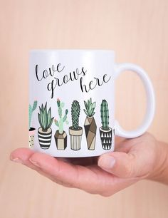 "This minimalist style coffee mug flaunts beautiful cacti plants wrapped around in geometric vases with the saying ""love grows here"". This is a sweet sentiment for any recipient or even for yourself! G"