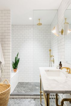 Monochromatic bathroom materials palette / White subway tile / Black hexagon floor tile / Polished brass plumbing fixtures / Pedestal sink with metal shelf / Shower curb tile application