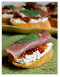 Crostini topped with goat cheese, fig jam, prosciutto ham and topped with fresh basil leaf...