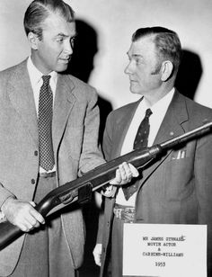 """James Stewart and David Marshall """"Carbine"""" Williams posing while Stewart holds an M1 carbine. Stewart starred in the 1952 film CARBINE WILLIAMS, portraying the life of its namesake who was a member of the Winchester Firearms team that designed and perfected the semi-automatic carbine used in World War II. While in federal prison, Williams invented the gas-operated system for the famous rifle, and he was eventually released early to work with Winchester on the new weapon."""