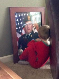 A mother captured this moment of her son tucked away in a corner with a picture of his father (SFC Benjamin Wise) who died in Afghanistan last January.