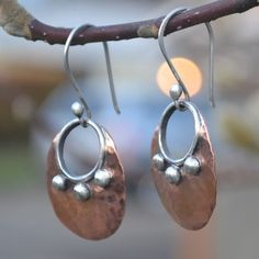 Hammered copper and sterling silver earrings that will catch the light and grab attention while hanging from your ears. These hand made mixed metal earrings combine the warm tones of copper, and the cool tones of sterling silver to create a beautiful earring. To add further interest to the earring I domed and patinaed the earring. I then polished the earring to bring out the shine. The earrings are finished with a hand formed sterling silver ear wire. The earrings hang at a total lenght…