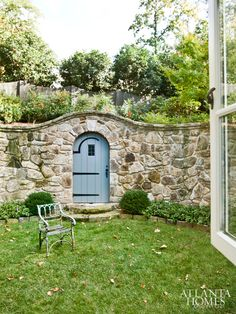 """""""Sunken"""" private back yard with tall stone retaining wall---grass below, and an antique door takes you to the upper yard with trees, shrubs, and flower borders"""