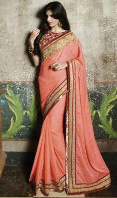 Sport a classy look with by draping this salmon color chiffon and jacquard embroidered sari. Beautified with lace and resham work. #peachcolorsaris #partywearsari #embroideredjardosiworksaree