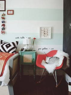 striped wall, accent table, black and white pillow and fun rocking chair