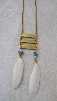 Aztec Boho Geometrical Necklace with two natural white feathes, two turquoise raw stones,three brass link charms, along with a brass chain.  You