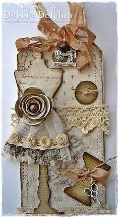 TOO CUTE TAG. . . .makes me want to go and pull out all my STUFF and put together several of these.   These TAGS start out as a plain, manilla shabby identification tag.    This one looks to be a collection of vintage buttons, pins, ribbon, stamping, charms, fabric, lace, paper & much more.  See the cute bell at top? Too cute!