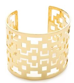 Interlocking logo cutouts lend geometric elegance to a wide Tory Burch cuff.