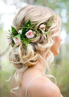 This crown of roses sits a top of a curled bun, with pieces pulled out here and there for an ethereal 'do.