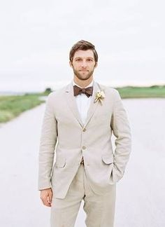 Groom with beard in khaki suit and brown bow tie