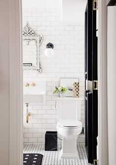 White tiled bathroom with white mirror and black door