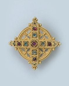A GOTHIC REVIVAL GEM SET BROOCH, BY CASTELLANI Designed as a cross set with cabochon emeralds and rubies to a circular background with trefoil piercework, enhanced with filigree borders, ormolu finish, circa 1860 With addorsed C's maker's mark for Castellani