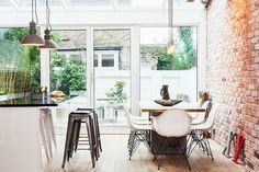 Sala de jantar com decoração em estilo industrial, moderna, com bancos de bar na cozinha de plano aberto e parede de alvenaria de tijolos exposta.