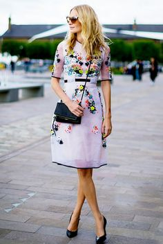 Poppy Delevingne wears an embroidered floral shift dress with a black bag, cat-eye sunglasses, and black pumps