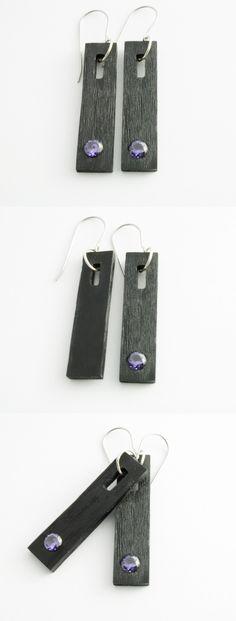 Ręcznie wykonane kolczyki z czarnego szkła akrylowego (pleksi) z ametystem o zabarwieniu fioletowym. Bigle zostały wykonane ze stali antyalergicznej. Długość kolczyka – 4cm Szerokość kolczyka – 1cm