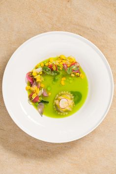 """Ravioli in BrodoRavioli in Brodo Centrifuging peas also produces a dense """"pea starch"""" substance and a light """"pea juice."""" Here, a ricotta-stuffed raviolo bobs in a pool of the bright green juice alongside corn kernels, radishes, fresh peas, and pea tendrils."""