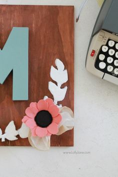 Make this pretty monogram sign out of a surprise material: foam! Cute home decor that's easy to make!  So cute with mixed media felt flowers and coffee filter leaves.
