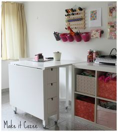 Use bins, buckets, and other containers to help keep all of your bits and bobbins organized in the sewing room. Great use of shelving and containers in this space!