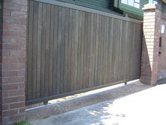 sliding gate … a little too modern for me but like how it is planked by the brick pillars