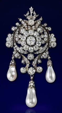 An impressive Victorian natural pearl and diamond brooch. Centring an old cushion-shaped diamond, set within a surround of ten smaller cushion-shaped diamonds and further scroll borders of graduated diamonds, suspending three natural pearl drops. With pendant fitting and detachable brooch fitting. #Victorian #antique #brooch
