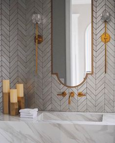 Marble like sink with chevron tile and good mirror and accents in bathroom.