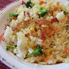 Quick Fried Rice | Cooked rice fried with egg, bacon, peas, carrots, and veggies.