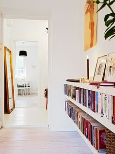 love a bookshelf in a hallway....lower shelving to leave room for art...