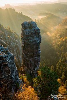 Felsnadel im Elbsandsteingebirge umgeben von golden glühendem Morgennebel und leuchtendem Herbstlaub