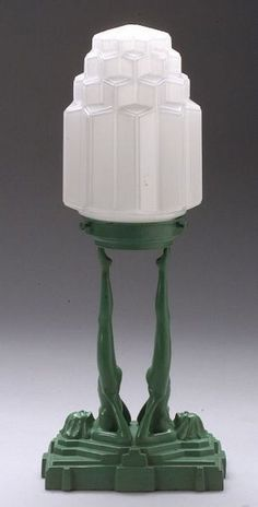 Art Deco Frankart table lamp  1928, patent 77202  Original stepped globe in white glass upheld by the outstretched legs of two female nude figures on rectangular base in green finish, Frankart mark, copyright dated with patent number, ht. with globe 19 1/2, shade aperture 3 7/8 in.