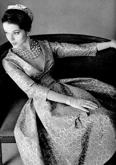 50's Model is wearing a gold leaf brocade dress with a deep decolletage by Jean Patou and necklace by Scemama.
