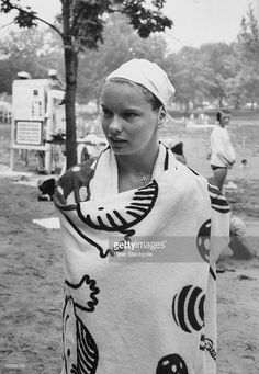 Swimming star Carin Cone wrapped in towel standing alone.