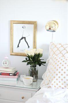 Un joli croquis de @Garance Lière Doré placé sous verre au dessus d'un table de chevet avec un reveil de style retro dans une chambre. Linge de lit motif pois en blanc et doré