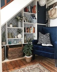Shelves under the stairs with wallpaper background, blue velvet chair reading nook Stair Bookshelf, Bookshelves, Under Stairs Nook, Cosy Reading Corner, Reading Nooks, Reading Areas, Reading Corners, Blue Velvet Chairs, Stairs In Living Room