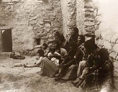 Hopi Life. It was created in 1907 by Edward S. Curtis.    The photo illustrates Several Hopi women and children seated on floor of unfurnished indoor structure.