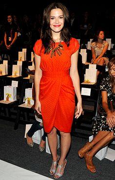 Bright orange dress and stick like necklace.