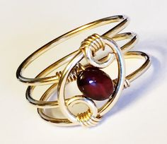 Garnet Ring Deep Red Garnet gemstone (6 mm) spiraled and wrapped in 14K Gold Filled wire . Garnet jewelry for the January birthstone birthday . Garnet Gold Ring makes a wonderful birthday , Valentines Gift or Christmas jewelry gift ! Ring sizes available 1-16 . Ring can be custom sized 1/2 or 1/4 sizes . Give size at checkout . Please provide correct sizing . Once made this ring type can not be re-sized . I also have other choices of wire 14K Gold , White Gold , Rose Gold , Brass...