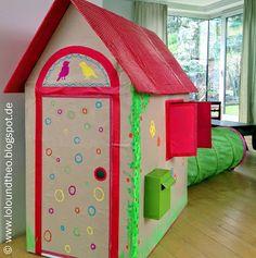 Ein kunterbuntes Spielhaus - selbstgemacht aus Pappkartons - mit Briefkasten und Tunnel als Hinterausgang