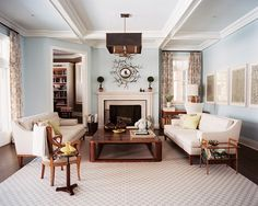 """My style in the Hamptons is a little different than my style in the city,"" explains the designer, ""I lean toward a more natural palette, more natural fibers, materials inherent to the landscape there."" In the expansive living room, shades of blue and sandy neutrals recall the seaside location, without relying on beach house tropes. Above the fireplace, a coral-like Hervé van Der Straeten mirror pops against walls in Benjamin Moore's Iceberg."