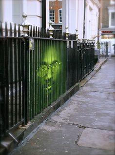 Visage peint sur barreaux d'une grille. Visible de biais uniquement.