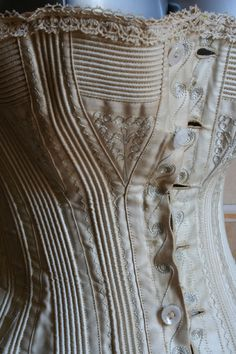 1878 bust detail - Corset in ivory satin with embroidery. The two front slats original and its hooks were removed and replaced with buttons. ____ (translated from Italian by Google)